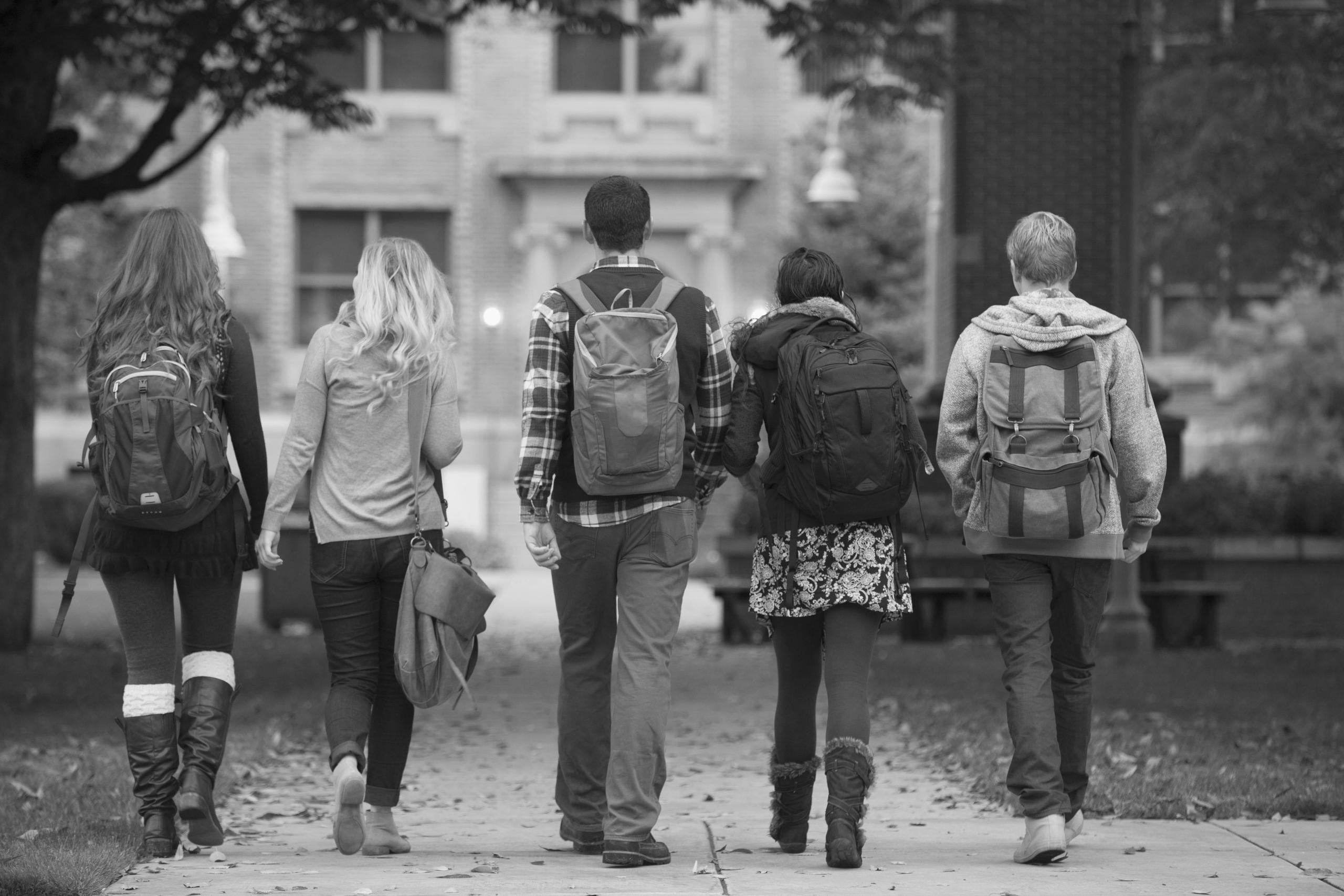 A group of five students with backpacks walking away