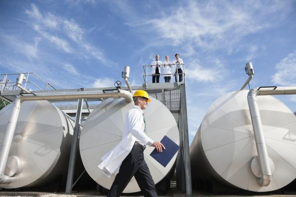Worker in lab coat walking in front of storage tanks