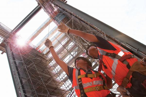 Two workers pointing up at scaffolding