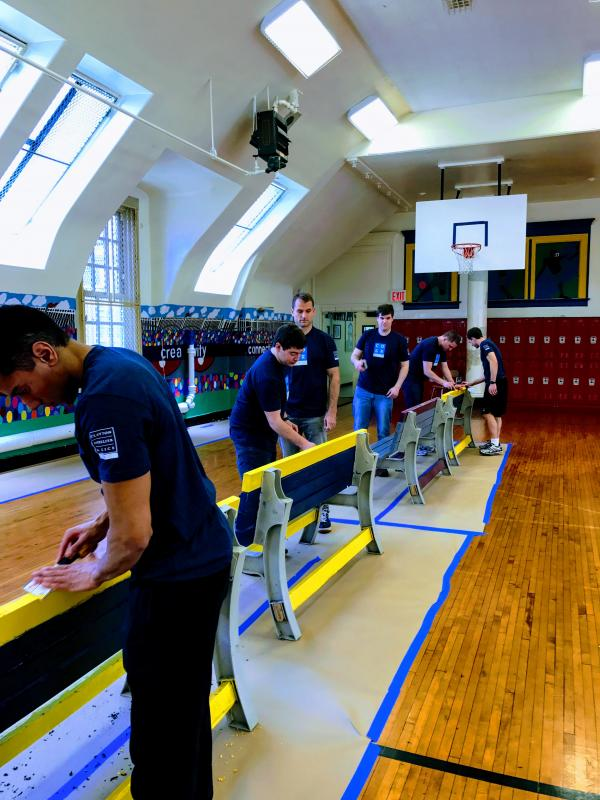 A group of men repairing and painting benches inside a gym