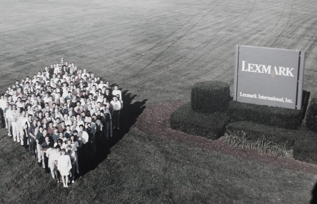 Lexmark employees standing in a group next to a Lexmark sign