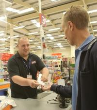 A male B&M cashier handing a receipt and change to a customer