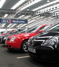 "Black and red cars parked in an indoor BCA parking lot with a sign above reading ""BCA Welcome"""