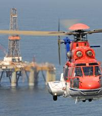 A helicopter flying away from an oil platform