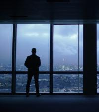 Silhouette of a man looking out of a window from a high floor