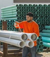 A worker taping together a group of four white industrial pipes
