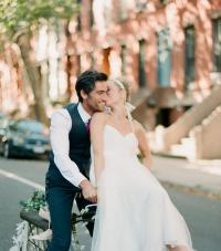 A bride and groom on a bicycle
