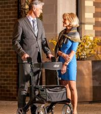 A man in a suit with a rollator walker talking to a woman outside