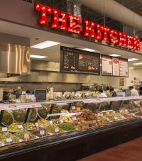 "The deli section of a grocery store with a sign above reading ""THE KITCHEN"""