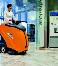 A worker riding a floor-cleaning machine