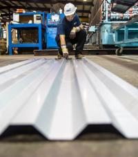 A worker inspecting a panel of corrugated metal