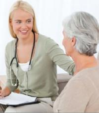 A woman with a stethoscope and a clipboard talking to an older woman