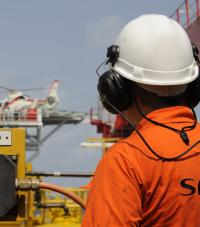 A worker in an orange SPIE shirt and white hardhat, with a helicopter in the background