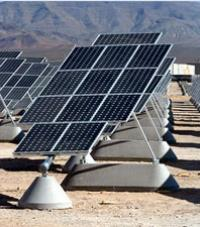 Many rows of solar panels with a desert mountain in the background