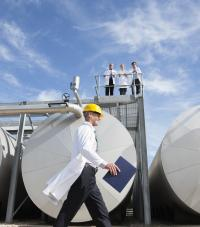 A worker in a white lab coat and hardhat walking in front of large storage tanks