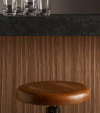 A bar stool in front of a bar countertop