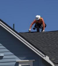 A man in a white hat working on the roof of a blue house