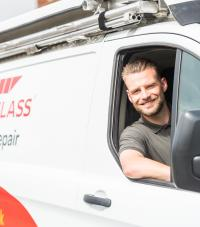 A smiling man leaning out of an Autoglass BodyRepair van