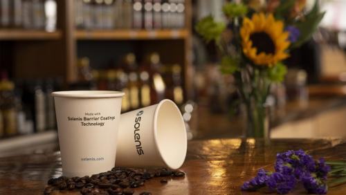 Two paper Solenis coffee cups with flowers and coffee beans
